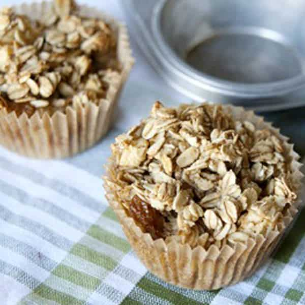 image: two muffins topped with oats sitting next to a muffin pan
