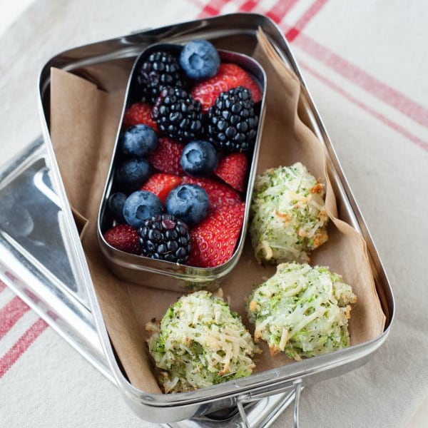 three broccoli tots in a small snack tin with berries.