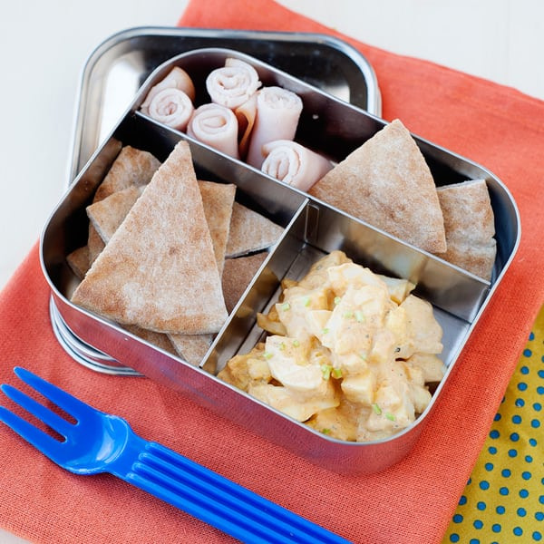 egg salad in a lunchbox with pita chips and turkey roll ups