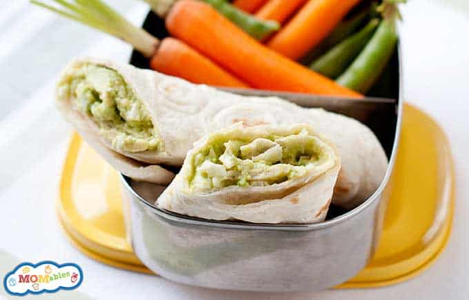Image: avocado egg salad wraps in a lunch container with carrots and sugar snap peas.