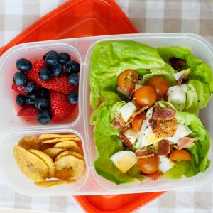 image: lettuce cup filled with chopped eggs, tomatoes, bacon and cheese in a lunch container.