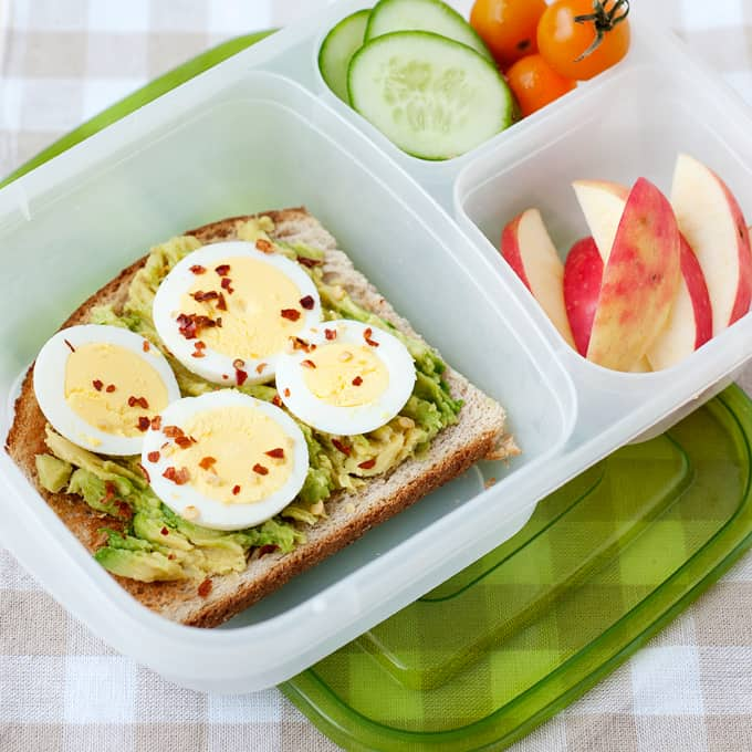 image: lunch container with avocado toast, sliced vegetables, and sliced apples