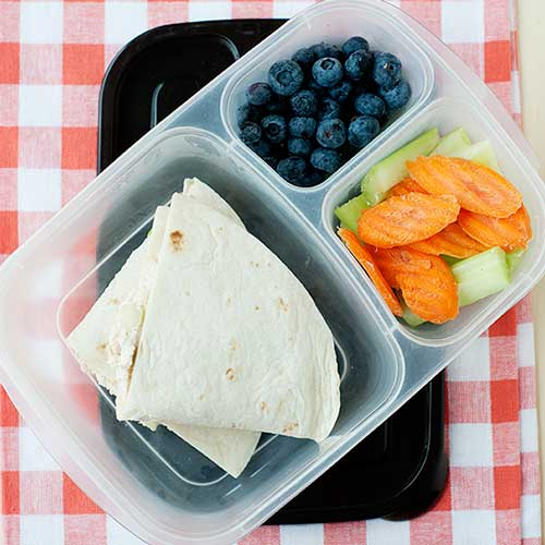 quesadillas in a lunch container with berries and chopped vegetables