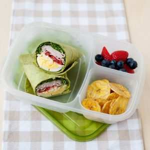 image: cobb salad wrap, banana chips and berries in a lunch container