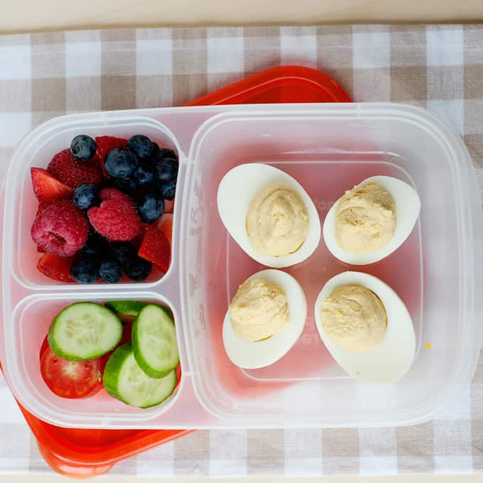 image: lunch container filled with deviled eggs, berries and sliced vegetables.