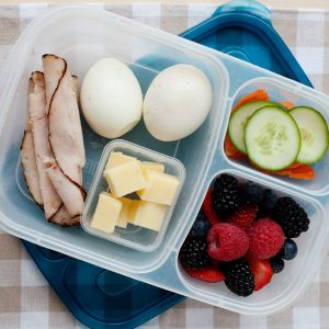 image: lunch container with turkey rolls, boiled eggs, cheese squares, sliced vegetables and berries.