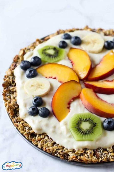 a fruit pizza made with an oatmeal cookie crust and topped with yogurt, sliced peaches, banana, kiwi, and blueberries.