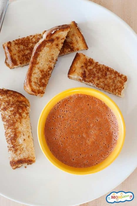 a bowl of tomato veggie soup with sliced grilled cheese sticks.