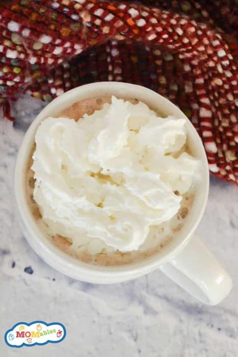 peppermint white hot cocoa in a white mug with whipped cream.