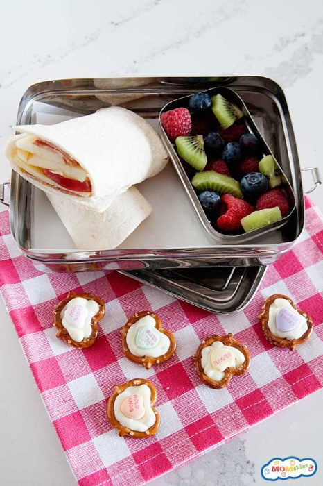 chocolate pretzel hearts on a pink and white cloth napkin next to a lunch container with an apple wrap and sliced blueberries, kiwi, and raspberries