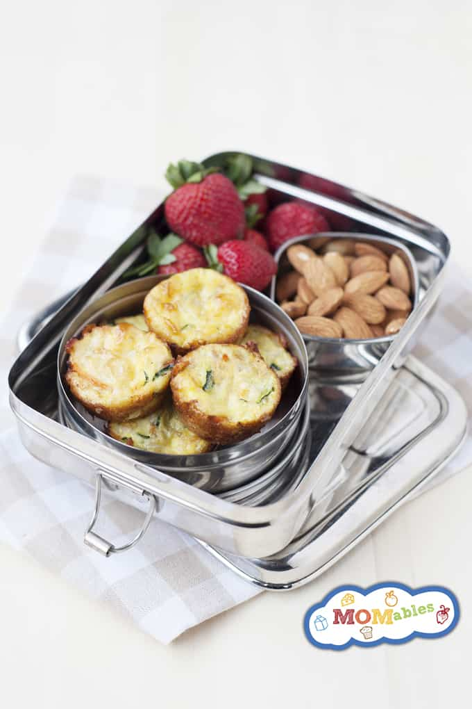 Image: carrot and zucchini mini quiches in a tin lunchbox with almonds and strawberries.
