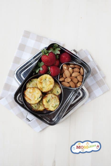 Image: overhead of carrot and zucchini mini quiches in a tin lunchbox with almond and strawberries.