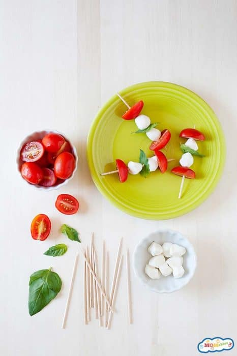 Images: tomato and mozzarella cheese skewers on a green plate with little bowls of tomatoes and cheese on the side.