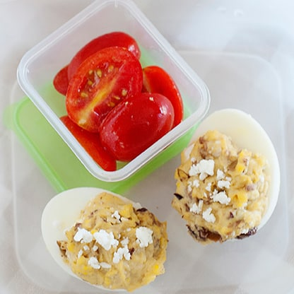 greek deviled eggs in a lunch container with halved grape tomatoes