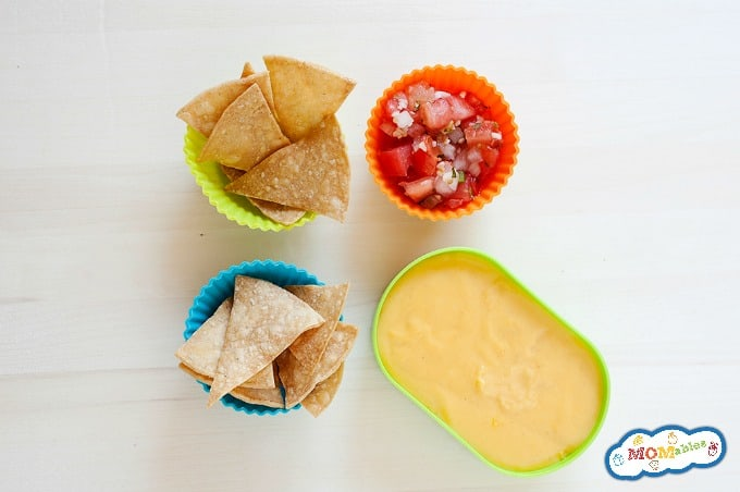 2 cups of tortilla chips served with a cup of pico de gallo and a cup of cheese sauce.