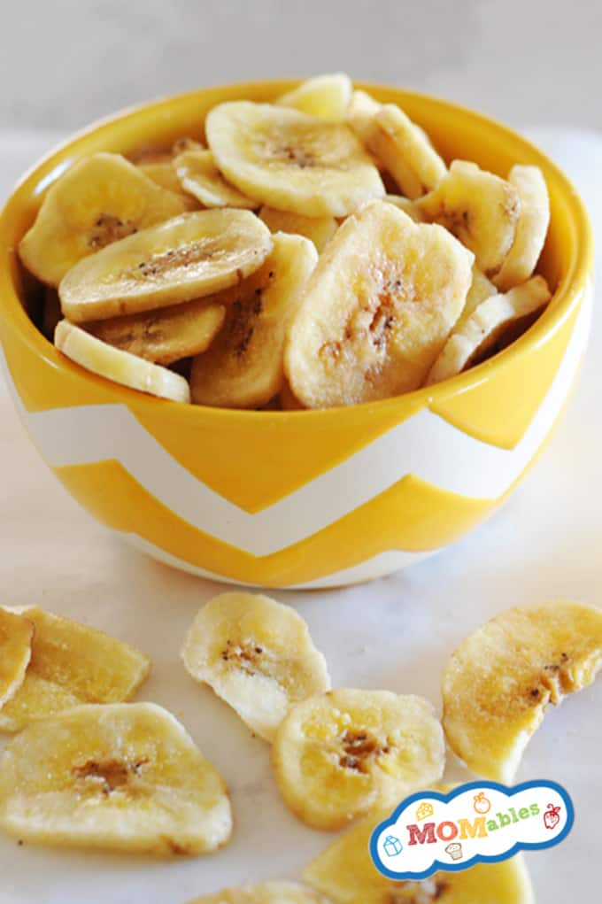Image: Yellow chevron bowl filled with baked banana chips with a few chips spilled out onto the counter.