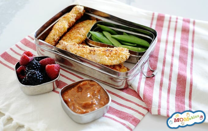 image: small lunchbox with four baked chicken tenders, and snow peas. Smaller containers hold dip and fresh berries.