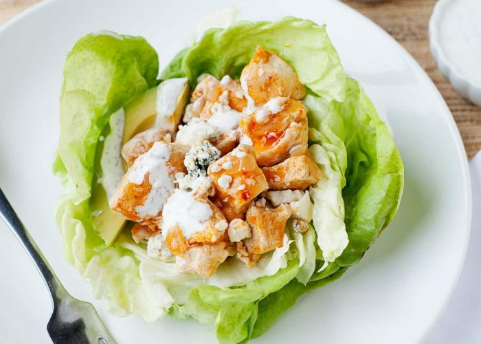 image: buffalo chicken on top of a bed of lettuce