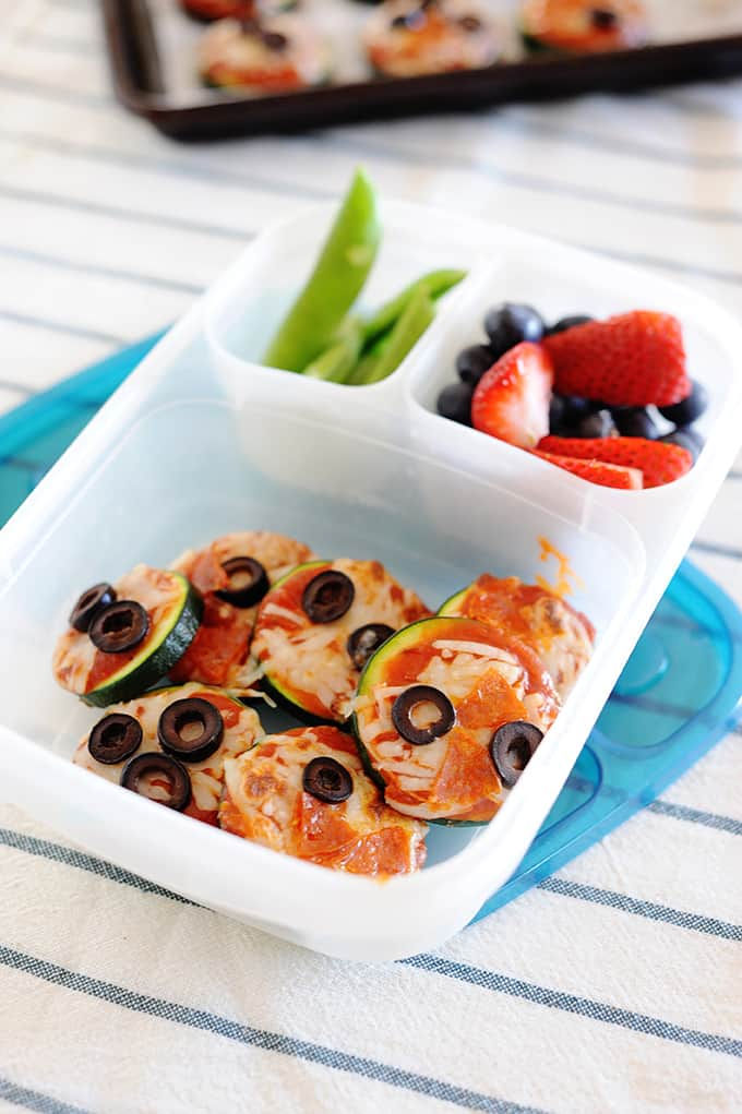 image: Pizza bites made with zucchini in a lunchbox container with berries and snow peas.