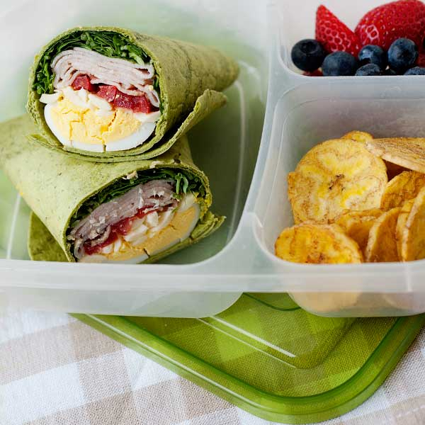 a green lunch wrap with plantain chips and fresh fruit