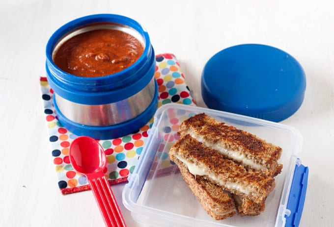 small blue thermos of red soup with sliced sandwich in small lunch container with red spoon