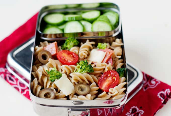pasta salad and cucumber slices in small silver lunch box with red bandana underneath