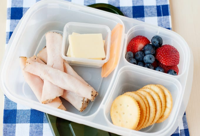round crackers, cheese and turkey slices and fruit in a divided lunch container