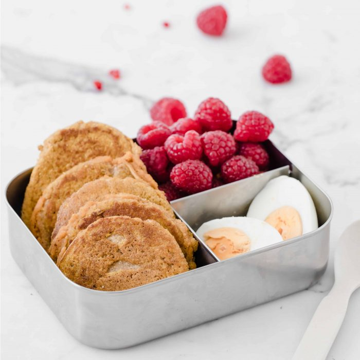 mini pancakes in a lunch tin with two boiled egg halves and raspberries