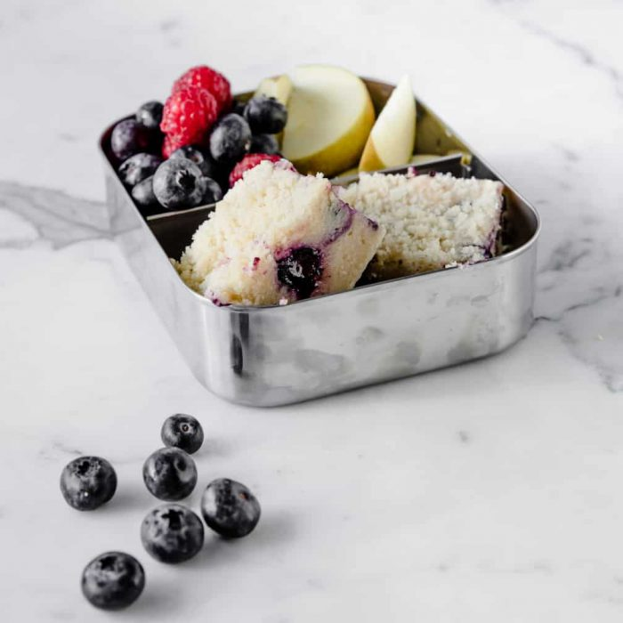 two small squares of blueberry coffee cake in a snack tin with fruit.