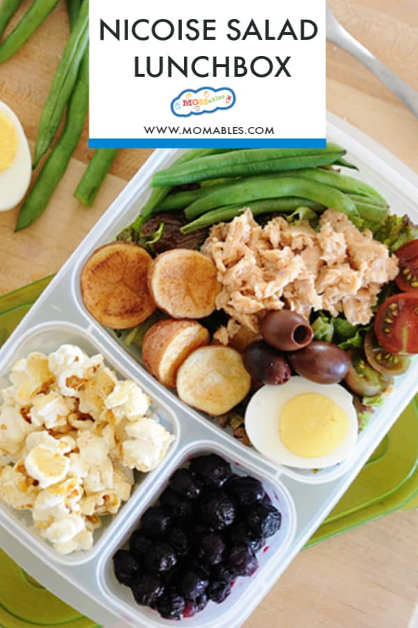 "image: salmon salad in a lunchbox with carrots, olives, green beans and tomatoes. Other portions of the lunch container filled with fruit and popcorn.   Image text reads ""Nicoise Salad Lunchbox"""