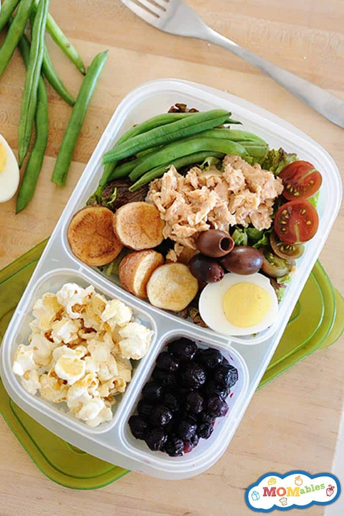 image: salmon salad in a lunchbox with carrots, olives, green beans and tomatoes. Other portions of the lunch container filled with fruit and popcorn.