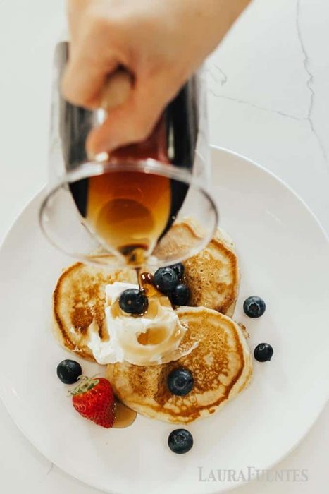 image: overhead shot of three pancakes on a plate topped with whipped cream and berries. Syrup being poured over the top.