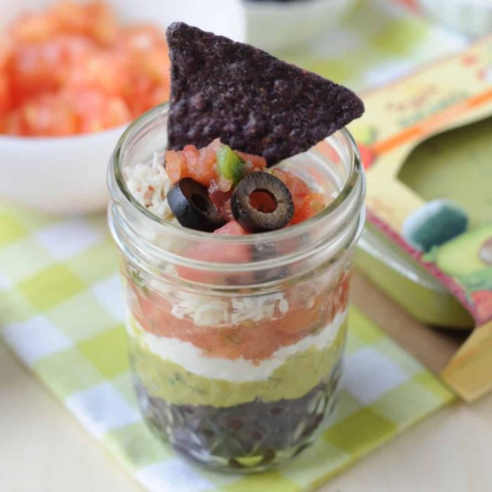 7 layer dip in a small mason jar with one blue corn chip in the top