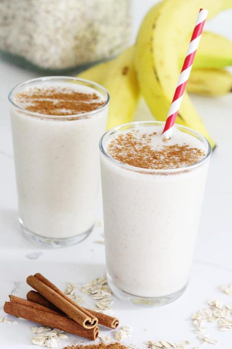 image: two smoothie cups with cinnamon sticks, bananas and oats