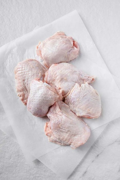 image: six raw chicken thighs on parchment paper