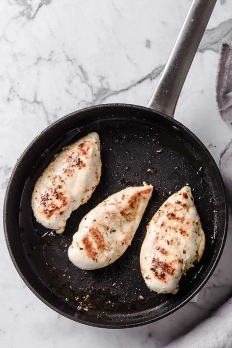image: three chicken breasts cooking in a frying pan