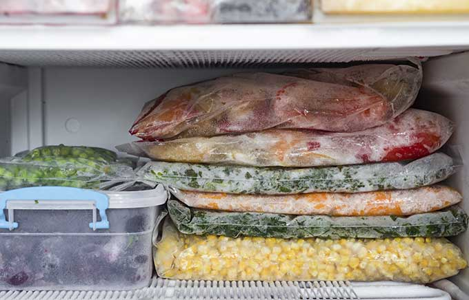 image: various foods bagged and frozen in a freezer