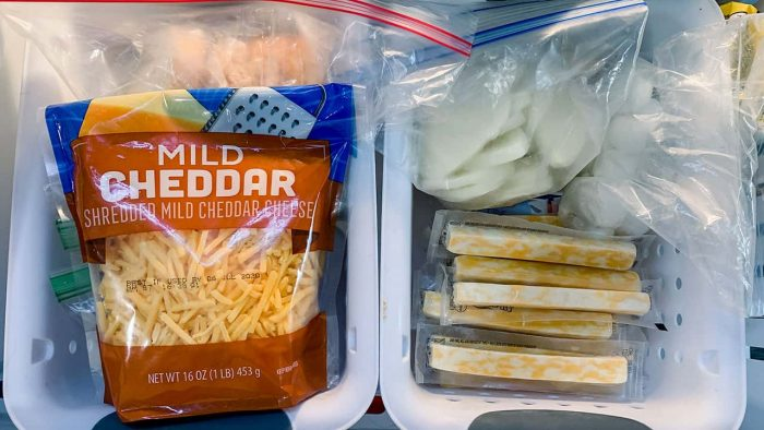 image: bag of shredded cheddar cheese and cheese sticks in a freezer drawer.