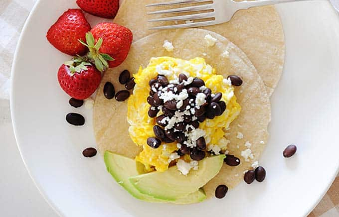 image: white plate of breakfast tacos with avocado slices and strawberries.