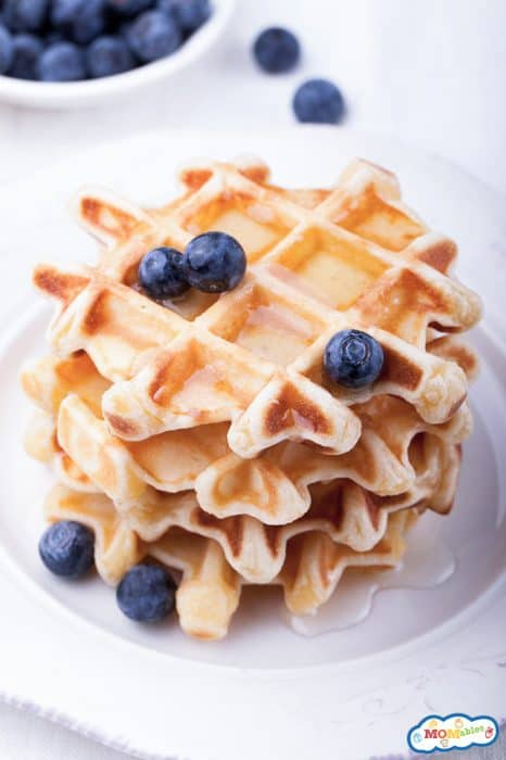 image: stack of four waffles on a plate with blueberries