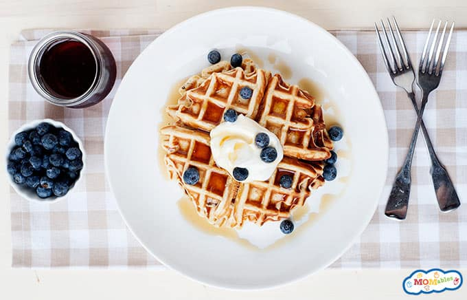 image: overhead photo of waffle on a plate with two forks, a dish of blueberries and a glass jar of syrup