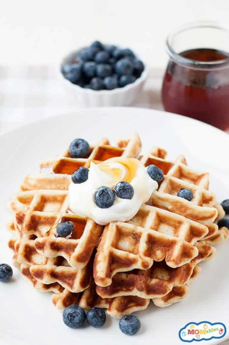 image: three waffles stacked on a plate with blueberries