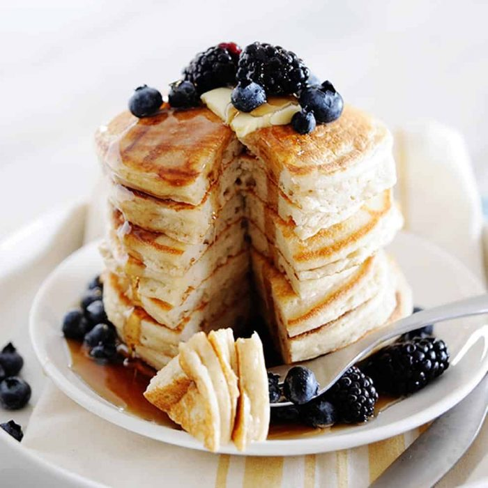 image: stack of pancakes on a plate covered in berries and syrup. One bite taken out.