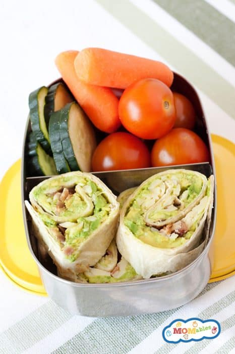 image: small lunch tin filled with sliced avocado pinwheels, cherry tomatoes, carrot sticks and sliced cucumbers.