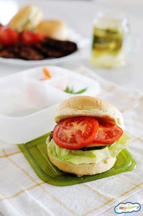 Image: a black bean veggie burger on a bun with lettuce and tomatoes.