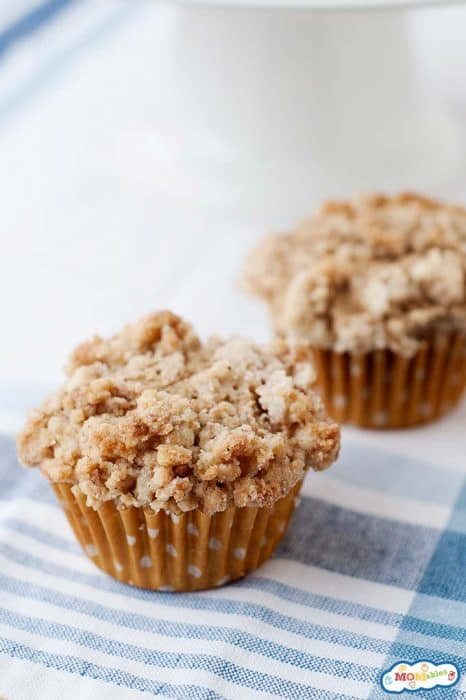 image: two cinnamon crumble muffins on a blue checkered tablecloth.