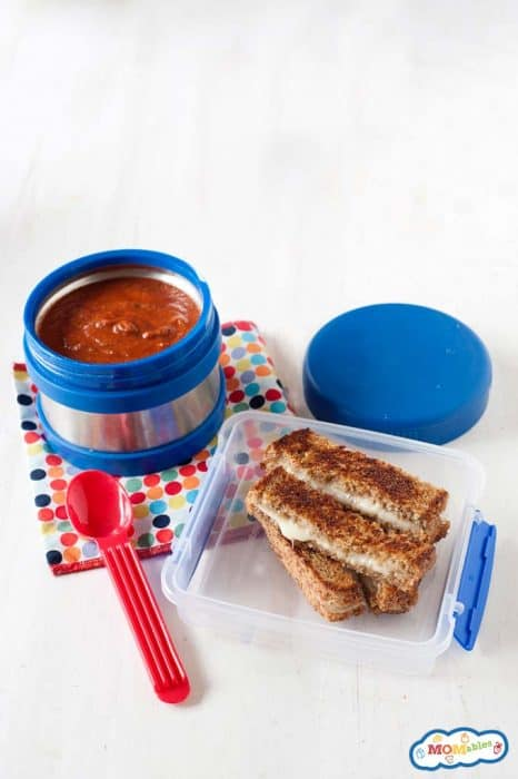 Image: overhead view of grilled cheese slices in a lunch container with a thermos of tomato soup on the side.