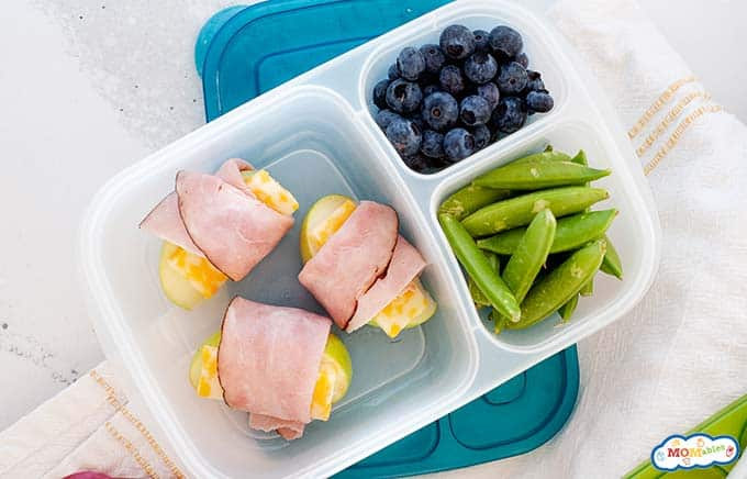 Image: closeup view of lunch container with blueberries, snap peas and apple & cheese slices wrapped with ham.