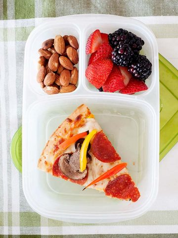 Image: Overhead of slice of pizza in a lunchbox with almond and fruit.