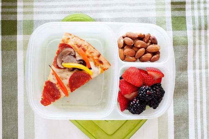 image: slice of pizza in a lunch container with berries and nuts.